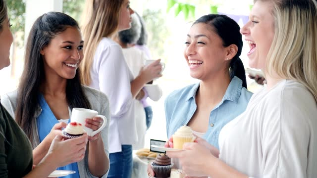 women enjoying time together at a charity bake sale - cupcake video stock e b–roll