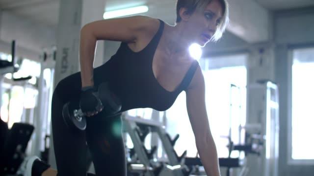 stockvideo's en b-roll-footage met vrouwen uitoefening van hijs halters in de sportschool - bankdruktoestel