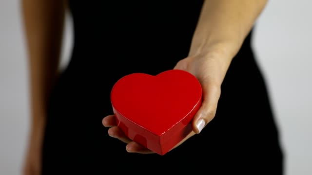 A women extends a gift in a red heart shaped box towards the camera and rejected