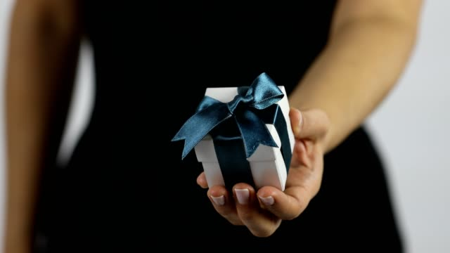 A women extends a gift in a white box with dark blue ribbon towards the camera A women is holding a gift on her palm. The gift is in a white giftbox with dark blue ribbon. She reaches the gift box towards the camera in order to give it. human relationship stock videos & royalty-free footage