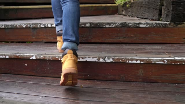 women feet wearing hiking boots walking up video