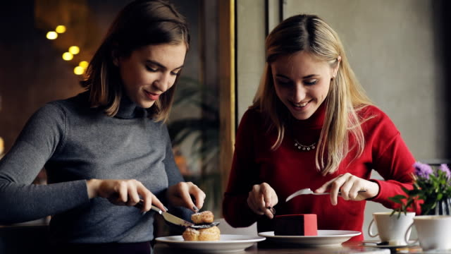 vídeos de stock e filmes b-roll de women friends enjoying eating cakes in cafe - bolo sobremesa