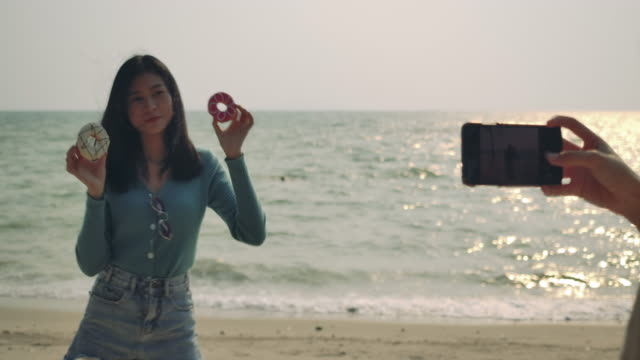 Women friends enjoying life eating donuts sweet delicious taking photos relaxing and freedom  at beach , Attractive together of asian female traveler people lifestyle. 4K UHD Footage cinematic.