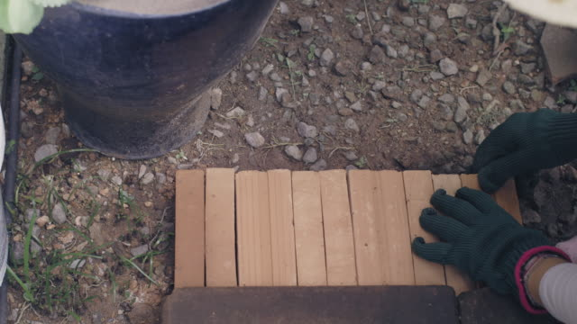 Women gardener decorate the garden using bricks to cover the walkway floor.