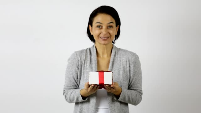 A women gets a present in a white gift box with red ribbon and admires to the giver