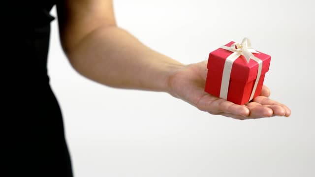 A women gives a present in red gift box with ribbon