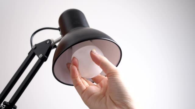 frauen hand installation glühbirne in schwarze moderne lampe. nahaufnahme handwechsellampe. konzept frauen tun männer hausarbeit. - led leuchtmittel stock-videos und b-roll-filmmaterial