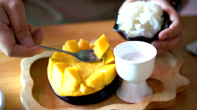 women hand scooping ripe mango video
