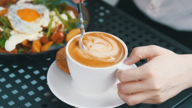 Women hand stirs coffee with a spoon