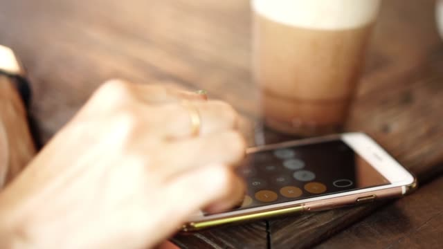 Women hand using smartphone for calculator at coffee cafe.