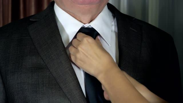 vídeos y material grabado en eventos de stock de manos de mujer correcta y apriete el nudo de la corbata hombre cuello y acariciando su chaqueta - corbata
