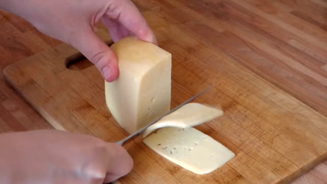 Women hands cutting cheese by metal khife video