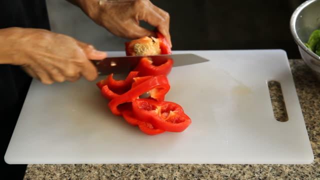 女性の手がキッチンにピーマンをスライスします。 ビデオ