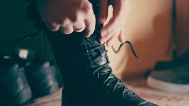 le mani delle donne legano i lacci delle scarpe su stivali in pelle nera high-top, da vicino - annodare video stock e b–roll