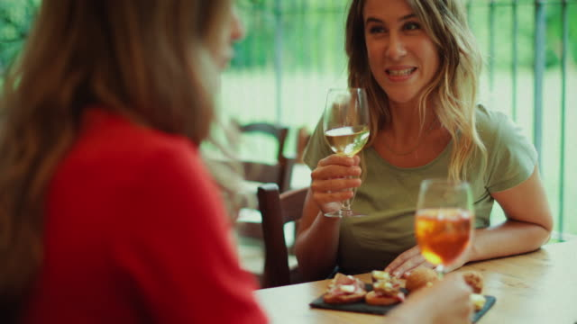 Women having Italian aperitivo together Women having Italian aperitivo together: drinking the typical Spritz cocktail, famous in North East of Italy. aperitif stock videos & royalty-free footage