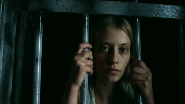 Women holding bars and looking through Young blonde women holding bars and looking through prison bars stock videos & royalty-free footage