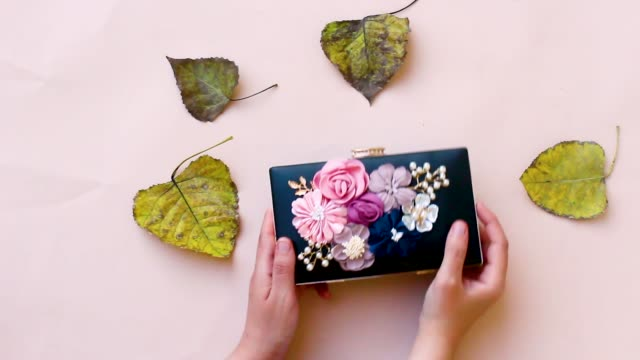 23419d36b9b women holding beautiful floral black clutch, wedding bag isolated on pink  background video