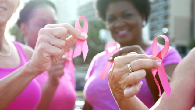 vídeos de stock e filmes b-roll de women holding breast cancer awareness ribbons - benefits