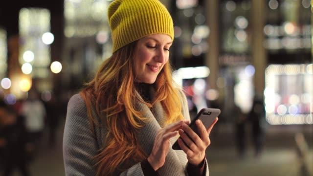 frauen halten smartphone und gehen auf der straße - einzelne frau über 30 stock-videos und b-roll-filmmaterial