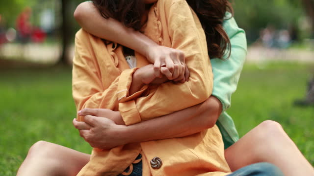 Women hugging and holding each other tight with arms