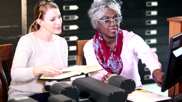 Women in library doing research with microfilm reader
