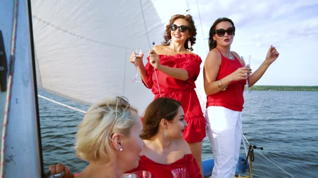 Women in red clothes drinking wine at sailboat party video