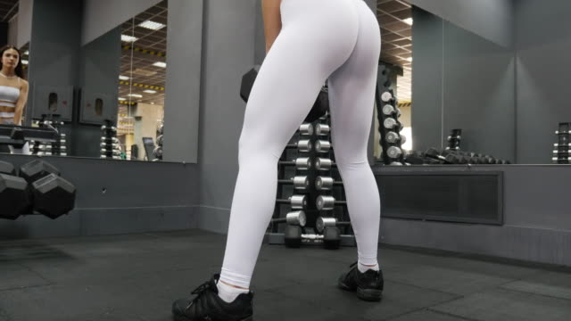 Women in Sport. Young beautiful girl is engaged on a fitness machine in the fitness center video