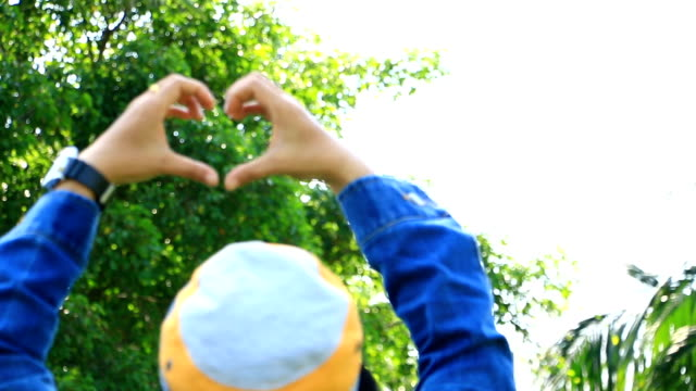 Women in striped shirt with denim coat is make hand to heart shaped. video