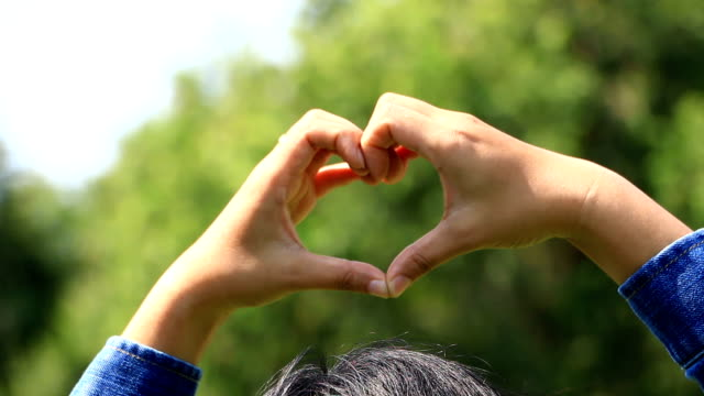 Women in striped shirt with denim coat is make hand to heart shaped, in the park. video