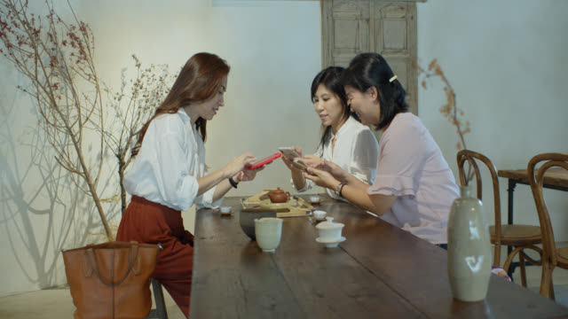 ティールームの女性は電話でお互いに写真を送ります - お茶の時間点の映像素材/bロール