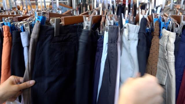 vídeos y material grabado en eventos de stock de mujeres en la tienda eligiendo jeans colgando en estantes - moda preppy