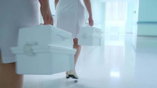 Women in white coats walk along the hospital corridor and carry a white box video