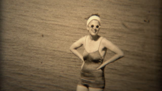 1938: Women in white round sunglasses and old timey bathing suit.
