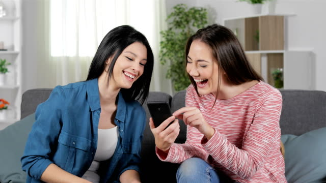 Women laughing reading smart phone content