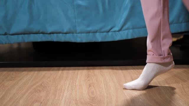 kvinnor ben i vita strumpor och rosa byxor smyga över sovrummet på golvet, parkett förbi sängen. närbild - på tå bildbanksvideor och videomaterial från bakom kulisserna
