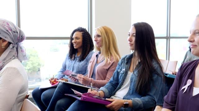 stockvideo's en b-roll-footage met vrouwen luisteren naar motiverende spreker tijdens borstkanker ondersteuning seminar - breast cancer