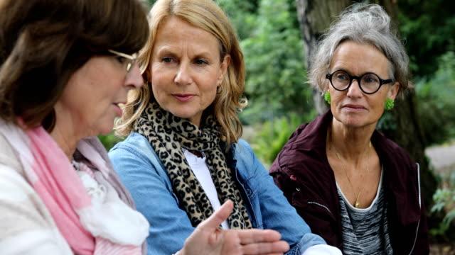 women listening to female friend talking in forest - amicizia tra donne video stock e b–roll