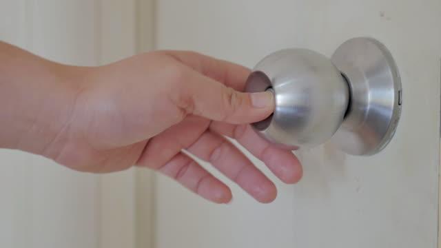 Women locks and unlocks his doorknob,Close-up