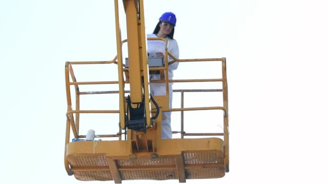 Women lowers an elevated platform using the control panel
