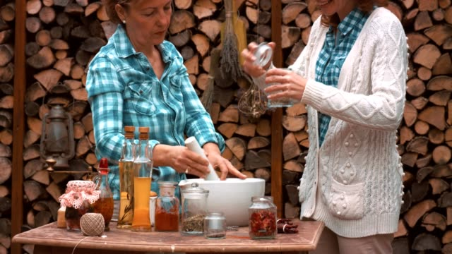 Women making natural parfumes Senior woman and her daughter are making an aromatic mixture of dry flowers and herbs. small business saturday stock videos & royalty-free footage