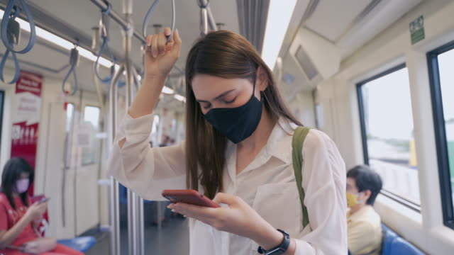 le donne di origine asiatica, di età compresa tra i 20 e i 30 anni, indossano abiti casual e utilizzano il servizio per utilizzare i mezzi pubblici, viaggiatori in ascensori in servizi di condivisione dei treni forme di viaggio sotto covid-19, riaprono i  - autobus video stock e b–roll