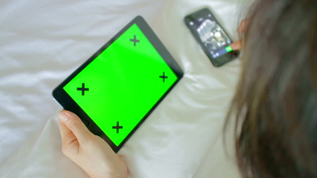 Women on bed using a Digital Tablet at home,Green screen video