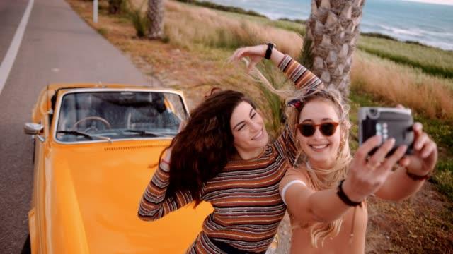 Women on island road trip taking selfies with polaroid camera