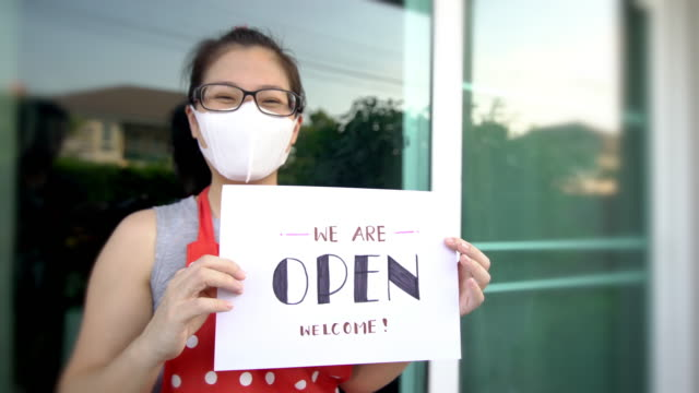 women owner holds open sign at front restaurant - open sign stock videos & royalty-free footage