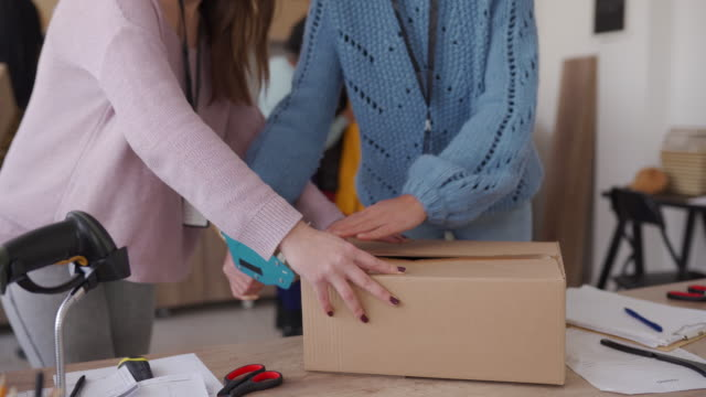 Women packing customers orders in cardboard box for drop shipping