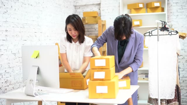 kadınlar kutularda mal paketleme - pazarcı stok videoları ve detay görüntü çekimi