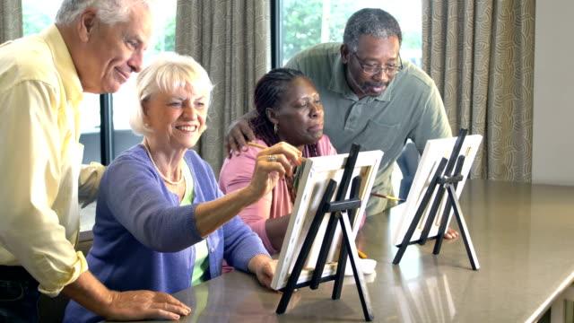 vídeos de stock e filmes b-roll de women painting pictures, husband watch - 55 59 anos