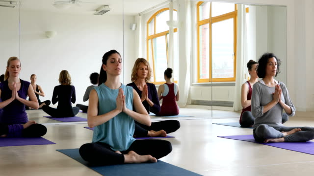 Women performing relaxation exercise in yoga class video