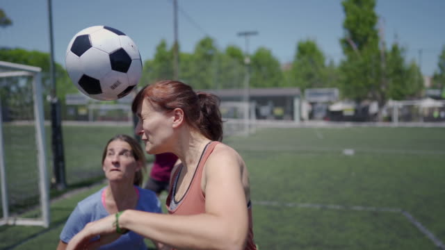 Women playing soccer outdoors