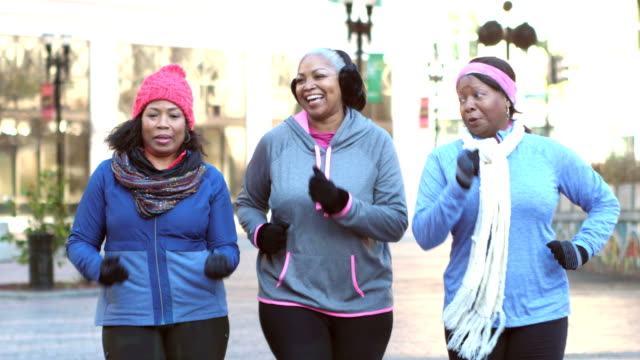 women power walking, talking, smiling in warm clothing - body positive video stock e b–roll